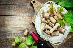 Grapes,a bottle of wine, corks and corkscrew on a wooden old table, rustic style Royalty Free Stock Photo