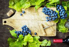 Grapes,a bottle of wine, corks and corkscrew on a wooden old table, rustic style Royalty Free Stock Image