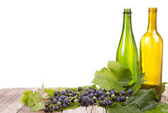 Grapes and bottles on wooden plank Royalty Free Stock Photos