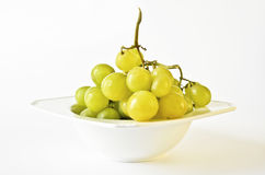Grapes in a bowl over white Royalty Free Stock Images