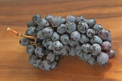 Grapes. A bunch of dark, black grapes lies on a wooden board close-up.  royalty free stock photography