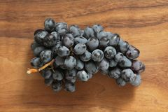 Grapes. A bunch of dark, black grapes lies on a wooden board close-up.  stock images