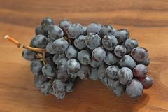 Grapes. A bunch of dark, black grapes lies on a wooden board close-up.  stock image