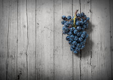 Grapes. Bunch of grapes on old wood and desaturated Stock Image