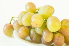 Grapes. A bunch of pink  on a white saucer and a white background Stock Image