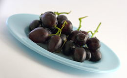 Grapes. A bunch of red grapes on a blue plate Stock Photography