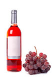 Grapes bunch and wine bottle. A red grapes bunch and wine bottle with blank label. White background with shadow stock photos