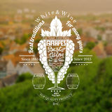 Grapes bunch with wineglass for text in the center on blurred background with vineyards and town Royalty Free Stock Image