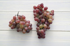 Grapes. Bunch of grapes on wooden table painted white Royalty Free Stock Photo