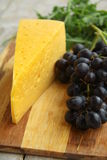 Grapes and cheese. Black grapes and cheese with herbs on a wooden board stock images