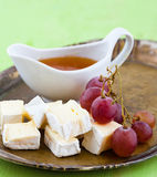 Grapes, cheese and honey on a tray. Cheese Served with grapes and honey on a plate Stock Photography