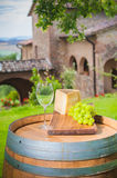 Grapes with cheese and wine. Cheese and grapes on a barrel in the Tuscan landscape Italy royalty free stock photo