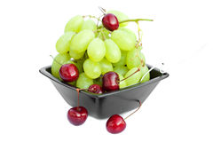 Grapes and cherries in a bowl isolated on white Royalty Free Stock Image