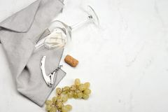 Grapes, corkscrew, wine stopper and glass with white wine. Still life on white background - top view, copyspace royalty free stock images