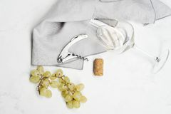 Grapes, corkscrew, wine stopper and glass with white wine. Still life on white background - top view stock images