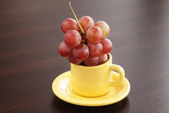 Grapes in a cup and saucer Royalty Free Stock Photos