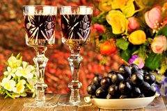 Grapes are a delicious delicacy and wine in a glass on the background of garden flowers and bokeh lights holiday. Wine in glasses royalty free stock image
