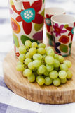 Grapes and drinks on cutting board Stock Photography