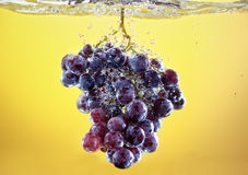 Grapes drop in tank filled with water Stock Photography