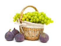 Grapes and figs isolated on a white background close-up. Ripe green grapes in a wicker basket and figs isolated on a white background close-up. horizontal photo Royalty Free Stock Photos