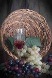 Grapes flowing from the basket. What better way to end a long day than to enjoy a glass of your favorite wine and freshly picked grapes straight from the Stock Image