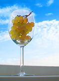 Grapes in a glass. Grapes bunch in a glass against blue sky with clouds stock images