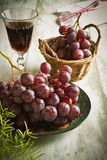 Grapes and a glass of wine. Fresh grapes and a glass of wine on the table. retro style.selective focus Stock Images