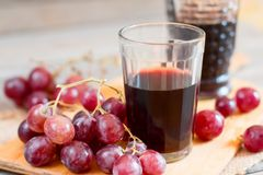 Grapes and a glass of wine on the table. Grapes and a glass of wine on a wooden table Stock Photos
