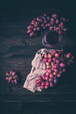 Grapes and a glass of wine. On a wooden background Royalty Free Stock Image