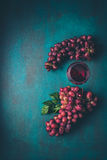 Grapes and a glass of wine. On a wooden background Royalty Free Stock Photo