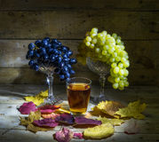 Grapes and grape juice. Still Life: Bunchs of white and black grapes, a glass of grape juice and autumn leaves Stock Photography