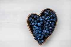 Grapes in a heart shape wooden plate. Close up Royalty Free Stock Photography