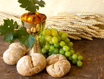 Grapes for holy wine. Grapes and holy bread next to a golden chalice with wine Stock Photography