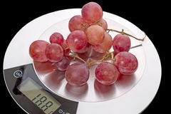Grapes on kitchen scale Stock Image