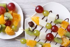 Grapes, kiwi and orange on skewers horizontal  top view Royalty Free Stock Photography