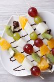 Grapes, kiwi, pear and orange on skewers vertical top view Stock Images