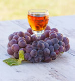 Grapes with leaf and glass of wine on wooden table in garden Stock Image