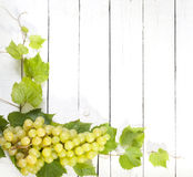 Grapes and leaves on vintage white planks Royalty Free Stock Images
