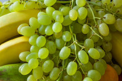 Grapes with other fruits. Bunch of green grapes with bananas and tangerine Stock Photo