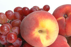 Grapes and peaches. Red grapes and luscious peaches  macro close up with a white background Royalty Free Stock Image