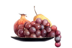 Grapes, pear and pomegranate isolated on white. Stock Photos