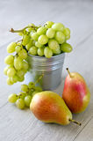 Grapes and pears. Autumn fruits in a bucket, wooden background Royalty Free Stock Photos