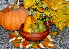 Grapes and pears lie on a plate, whole pumpkin, autumn colorful leaves royalty free stock photo