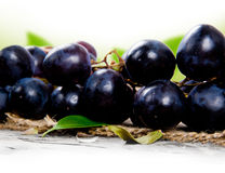 Grapes. Photo of grapes on burlap and wooden board with white space Royalty Free Stock Photography