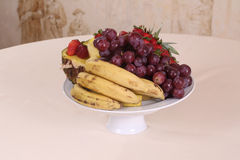 Grapes, pineapple, bananas and fresh strawberries on the plate Royalty Free Stock Image