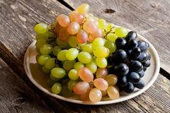 Grapes on a plate on a old wooden table. stock image