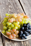 Grapes on a plate on a old wooden table. stock photo