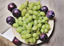 Grapes and plums on a plate on a wooden background Royalty Free Stock Images