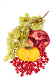 Grapes, a pomegranate and a persimmon Royalty Free Stock Photo
