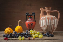 Grapes and pumpkins with ceramic jugs Royalty Free Stock Photo